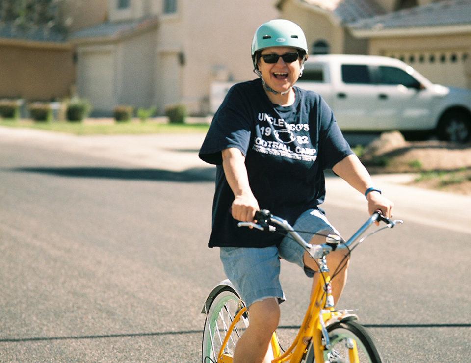 Mature senior woman riding a bike happy